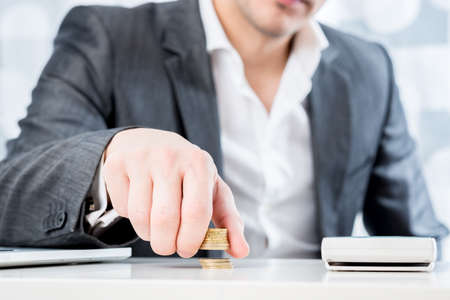 bank deposit: Successful businessman sitting at his desk counting gold coins in a conceptual image, closeup view of his torso with focus to his hand.