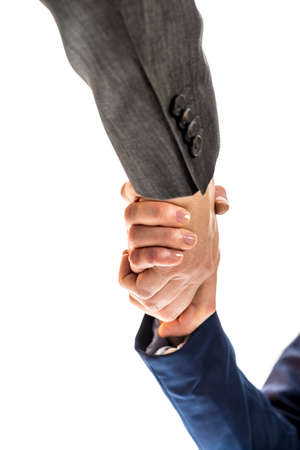 Businessman and woman shaking hands to close a deal, in partnership, greeting or congratulations, view from underneath their hands isolated on white. photo