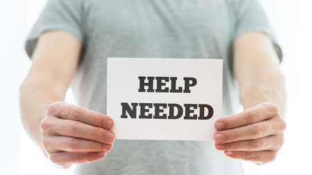 needed: Man in a grey t-shirt holding a white card with Help needed sign representing a job offer or problematic of homeless people. Stock Photo