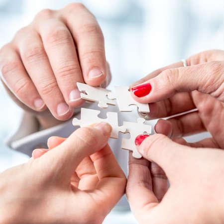 흰색 퍼즐 조각을 조립하는 개념적 인간의 손에의 총을 닫습니다.