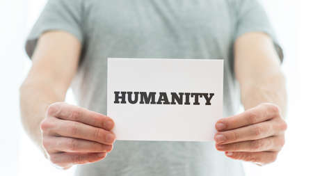 agape: Closeup of a man holding white card with Humanity sign on it.