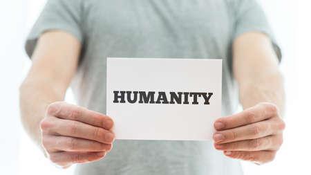 humanidad: Primer plano de un hombre que sostiene la tarjeta blanca con el signo humanidad en �l. Foto de archivo