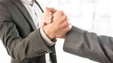 business teamwork: Close up Conceptual Two Businessmen in Gray Business Suit Gripping Their Hands at the Office.