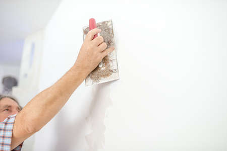 parget: Man plastering a white wall preparing it for painting or wallpapering in a DIY and home decoration or renovation concept.