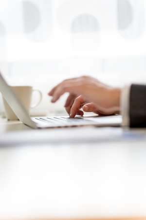 furthest: Man typing in information on his laptop with selective focus to the hand furthest from the camera, side view of both hands on the desk. Stock Photo