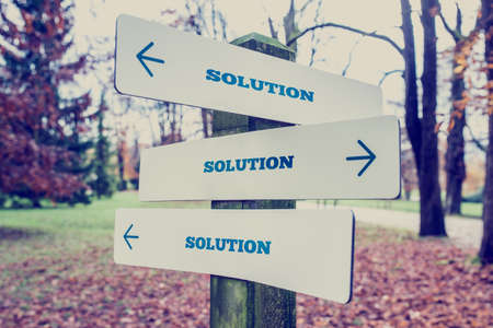 Retro effect faded and toned image of a rural signboard with the word Solution with arrows pointing in three directions.
