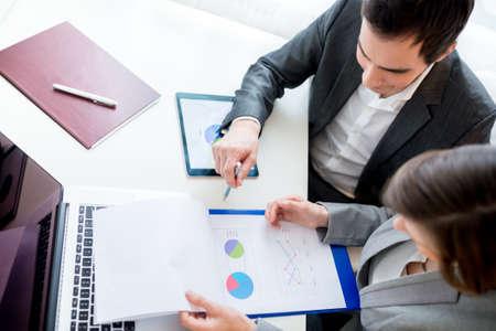 revisando documentos: Vista aérea de dos personas de negocios revisión de las historias de Documentos comerciales mientras estaba sentado en la mesa de trabajo.