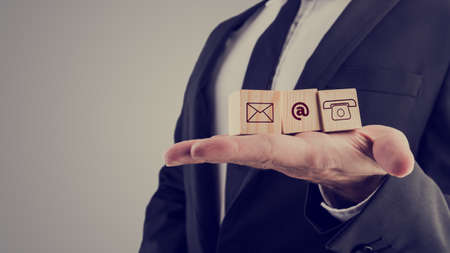 Retro style image of a businessman holding three wooden cubes with contact symbols - envelope, at sign and telephone - conceptual of communication and business support. Foto de archivo