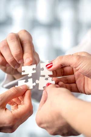 Four hands fitting together matching interlocking puzzle pieces conceptual of teamwork and problem solving. photo