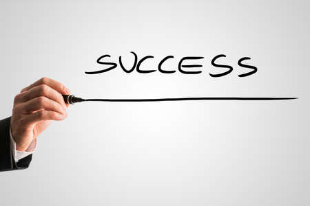 successfulness: Man writing the word - SUCCESS - with a black marker pen from behind a virtual screen or interface on a light grey background with copyspace, close up view of the text and his hand. Stock Photo