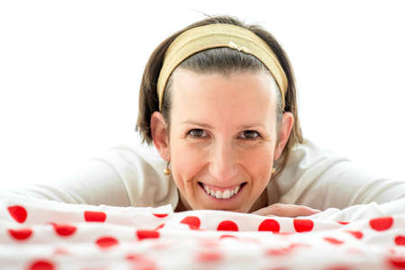 counterpane: Smiling happy attractive woman lying on a colorful red polka dot counterpane on a bed facing the camera with a friendly warm smile.