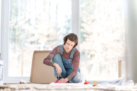 Young woman doing DIY repairs at home putting together self assembly furniture using a screwdriver.