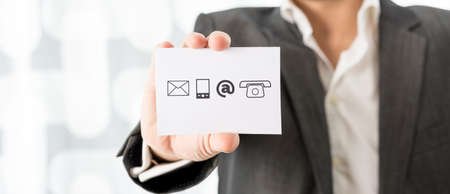Closeup of businessman showing a white card with contact icons. Conceptual of business information center and support. photo