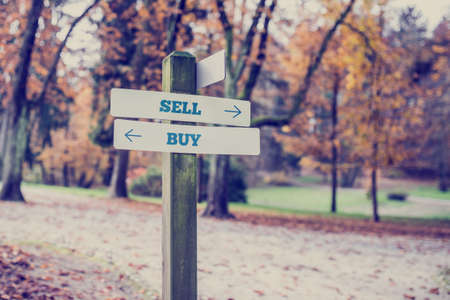 the conceptual: Retro style image of a rural signboard with two signs saying -  Sell - Buy - pointing in opposite directions. Stock Photo