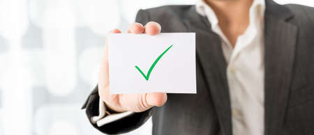 legitimate: Closeup of businessman or teacher holding up a white card with green check mark. Conceptual of successfully completed task or homework.