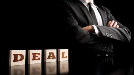 pacto: Hombre de negocios con los brazos cruzados en una imagen conceptual de éxito y poder acuerdo de negocios con los cubos de madera de deletrear la palabra DEAL. Sobre fondo negro.