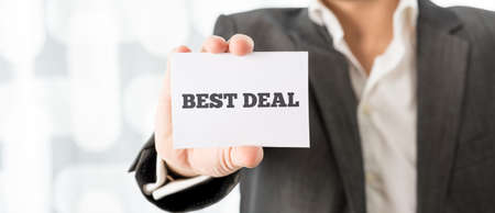deal in: Businessman holding a small white business card with the words - Best Deal - in a promotional concept of the best offer, close up of his hand.