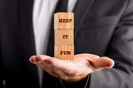 dinamismo: Imprenditore in possesso di tre cubi di legno allineati verticalmente, con Keep it divertimento segno, concetto di dinamismo, divertimento e atmosfera positiva.