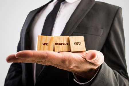 respeto: El hombre de negocios la celebración de tres cubos de madera o bloques de construcción en la palma de la mano con las palabras - Le respetamos - en una imagen conceptual. Foto de archivo