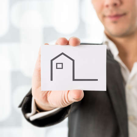 Businessman holding up a house icon on a card in a conceptual image of real estate, agent or broker, ownership or insurance, close up of the card. photo