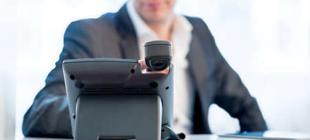 Close up view across the desk of the hands of a businessman making a  phone call as he sits at his desk in a communications concept. photo
