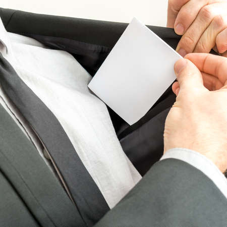 Businessman removing or placing a blank white business card in the inner pocket of his suit jacket, close up view of the card with copyspace. photo