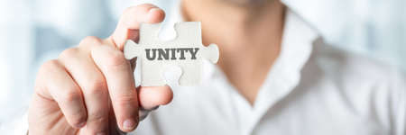 entity: Businessman Showing a Conceptual White Jigsaw Puzzle Piece with Unity Text in Close up.