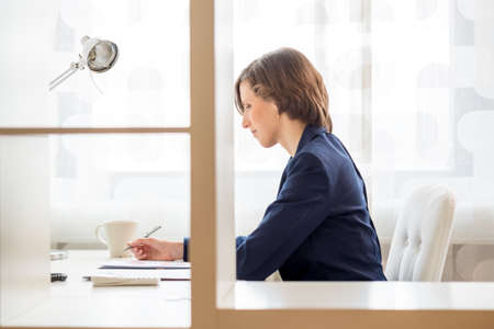 glass partition: View through an interior glass partition of a businesswoman working in an office sitting at her desk in profile. Stock Photo