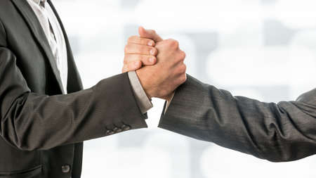 griping: Close up Shot of Conceptual Two Business Partners in Gray Formal Suits Gripping their Hands. Stock Photo