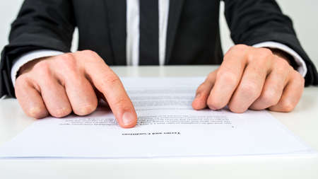 terms: Closeup of a lawyer or a real estate agent proofreading Terms and conditions document.