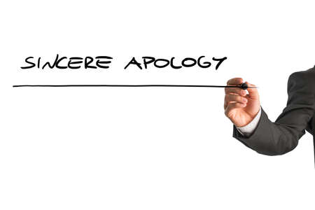 apology: Closeup of male hand writing Sincere apology on white virtual screen.
