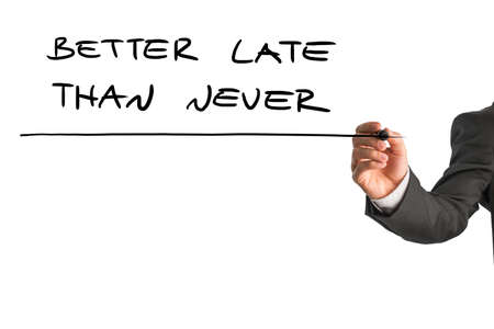 better chances: Man writing the words - Better late than never - with a black marker pen from behind a virtual screen or interface on a white background with copyspace, close up view of the text and his hand.