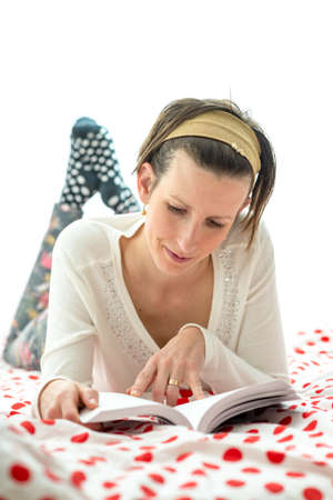 counterpane: Attractive woman spending a relaxing day at home lying on a colorful red polka dot counterpane on her bed reading a novel.
