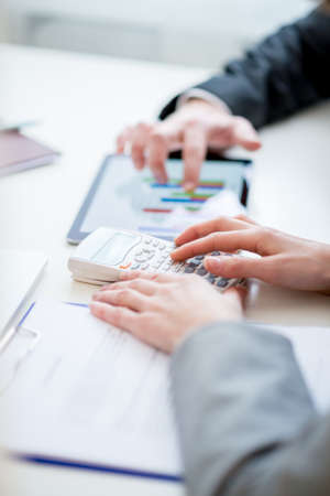financial graphs: Two business colleagues, a man and woman, comparing and checking statistical business graph and data on a tablet computer as they sit side by side at the desk. Stock Photo