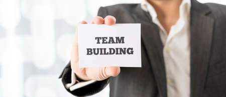 clarifying: Close up Businessman Showing a Conceptual Small White Card with Team Building Texts on a Blurred Abstract Background.