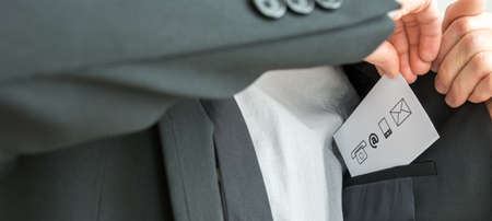 Businessman removing a business card with communication icons - phone, email, web address and mobile - from the inner pocket of his jacket, close up view. photo