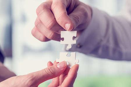 comunidad: Imagen de estilo vintage retro de un empresarios encajando a juego entrelazados piezas del rompecabezas conceptual del trabajo en equipo y resoluci�n de problemas.
