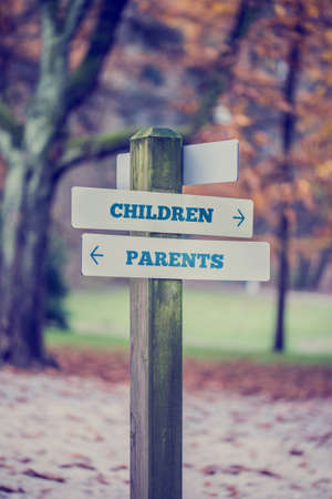 separate: Signpost in a park or forested area with arrows pointing two opposite directions towards Children and Parents. Conceptual of a fun adventurous day with separate activities for the kids and adults. Stock Photo