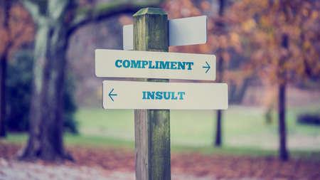 falta de respeto: Imagen de estilo vintage retro de un cartel rural con dos carteles que dec�an - Elogio - Insulto - apuntando en direcciones opuestas.