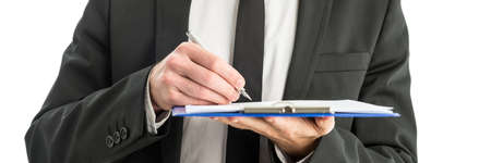 observations: Closeup of businessman holding blue clipboard folder writing notes and observations with ink pen.