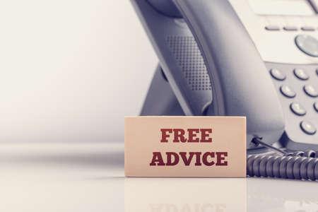 Retro effect vervaagde en gestemd beeld van een klassieke vaste telefoon met een houten kaart ernaast met gratis advies teken. Conceptuele van gratis juridisch advies en consulting.