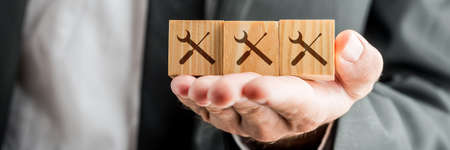 Close up Conceptual Businessman Showing Wooden Blocks on his Hand with Service Tools Prints.