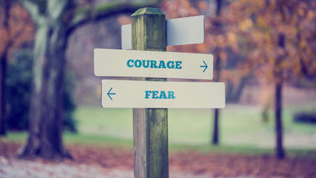 Retro style image of a rustic wooden sign in an autumn park with the words Courage - Fear offering a choice of reaction and attitude with arrows pointing in opposite directions in a conceptual image. Foto de archivo