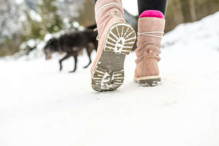 Close up Light Brown Winter Shoes of a Woman Walking on the Snow.