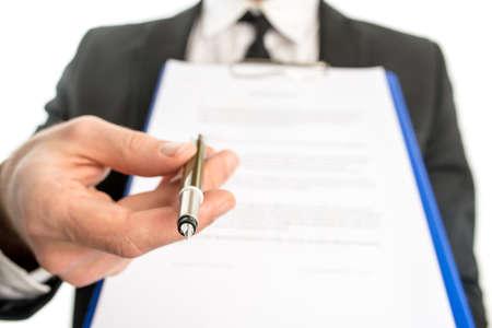 Zakenman of verkoper overhandigen van een contract bevestigd aan een klembord voor ondertekening met een balpen in de hand met de focus op de pen.