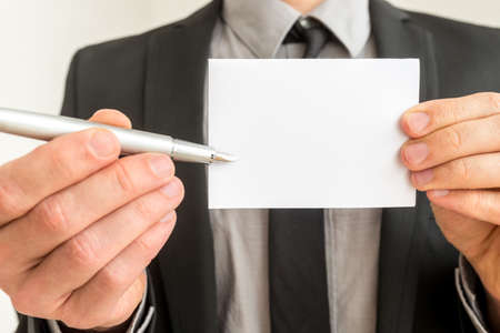 businesscard: Businessman holding out a blank card and pen for you to write your contact details or business name, close up of the card and pen.