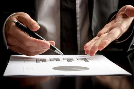gerente: Hombre de negocios en una reuni�n o presentaci�n que sostiene una pluma en una mano y se�alando con la otra a un documento sobre la mesa frente a �l, vista de cerca. Foto de archivo