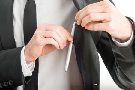 hands in pocket: Businessman removing a pen from the pocket of his suit jacket, close up view of his hands and the pen.
