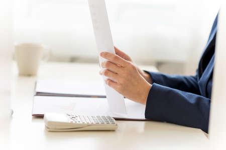 그녀의 화이트 계산기와 작업대와 커피 컵에서 문서를 작성하는 사업가의 근접 촬영입니다. 사무실 내부 캡처. 스톡 콘텐츠