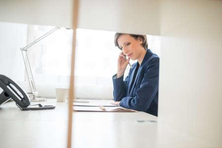 secretaria: Ver a través de una partición interior de una atractiva empresaria trabajando duro en la oficina sentado leyendo el papeleo en su escritorio.